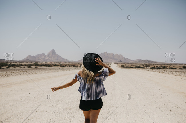 Namibia- woman walking on the road to Spitzkoppe
