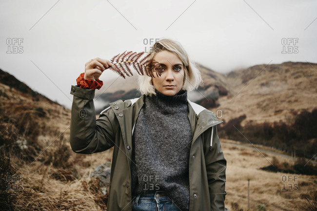 UK- Scotland- Highland- portrait of young woman holding fern