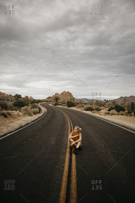 Woman sitting on road- Joshua Tree National Park- California- USA