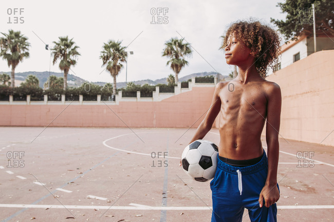 Boy holding a soccer ball standing on a soccer field