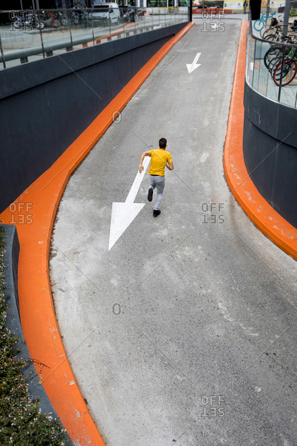 Young man running on road- against the direction of arrow sign