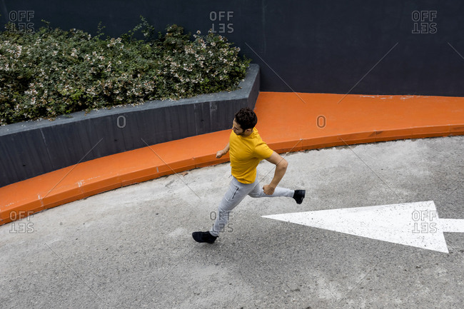 Young man running on road- in direction of arrow sign