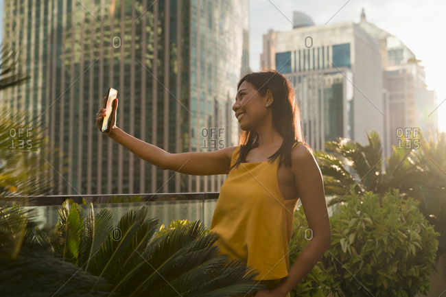 Smiling woman standing on roof terrace in the evening taking selfie with smartphone- Bangkok- Thailand