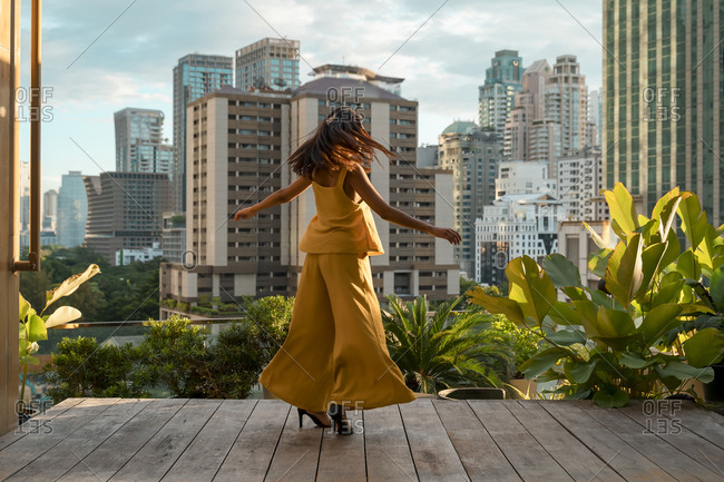 Back view of woman dancing on roof terrace- Bangkok- Thailand