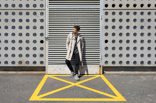 Mid adult man waiting in yellow marked area in front of concrete wall