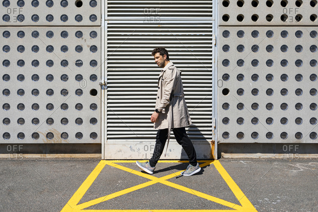 Impatient man walking in yellow marked area in front of concrete wall