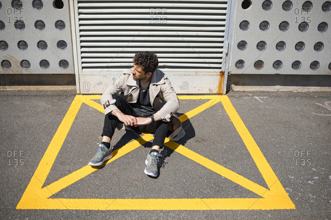Helpless man sitting on ground in yellow marked area in front of concrete wall