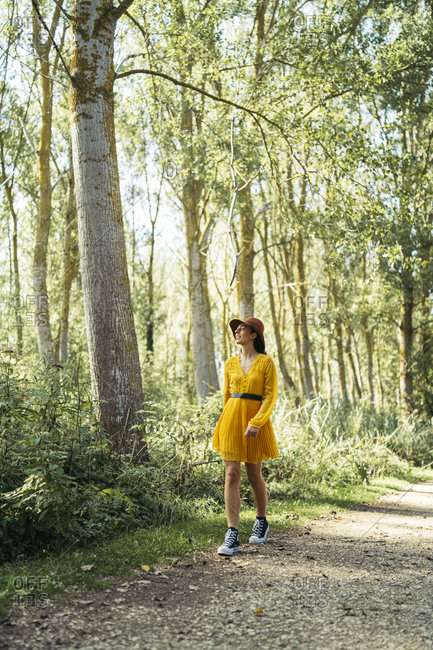 Young woman wearing brown hat- yellow dress and black sneakers looking up and walking in forest