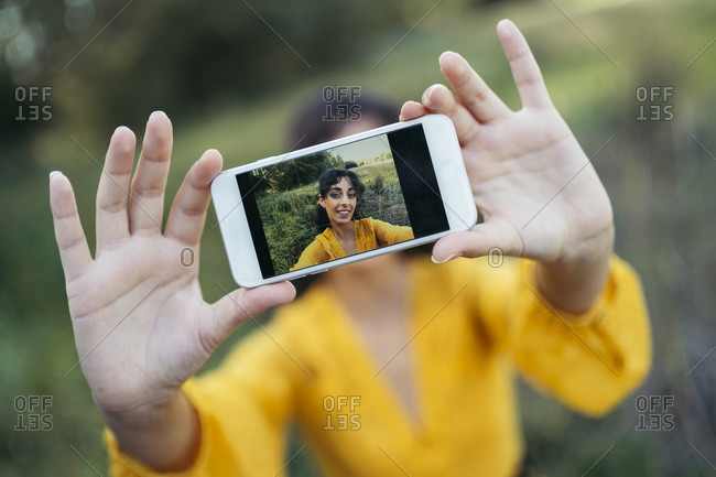 Happy young woman wearing yellow dress taking a white smartphone in front of her face and taking a selfie