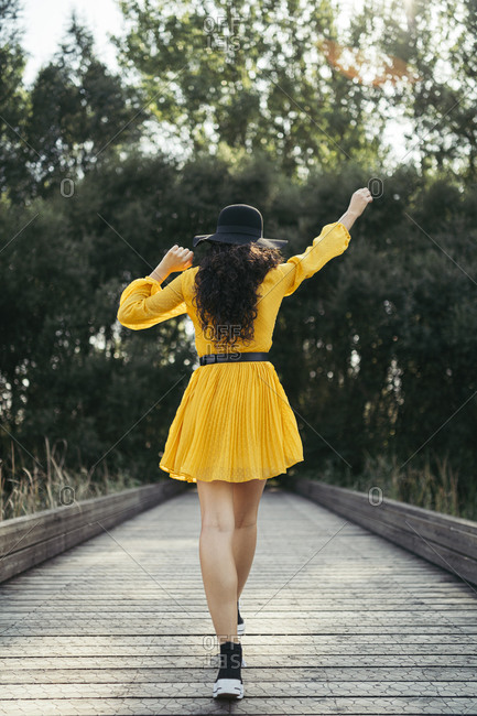 Rear view of a young woman wearing black hat and yellow dress enjoying while is walking along wooden bridge