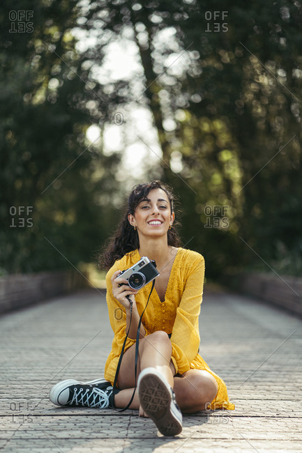 Young female photographer wearing yellow dress and black sneakers holding an analog camera on wooden boardwalk