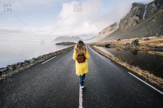 Iceland- back view of woman with backpack walking on median strip of country road
