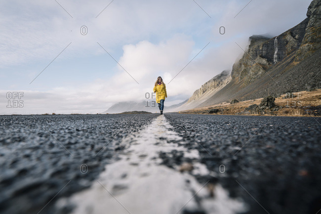 Iceland- woman walking on median strip of country road