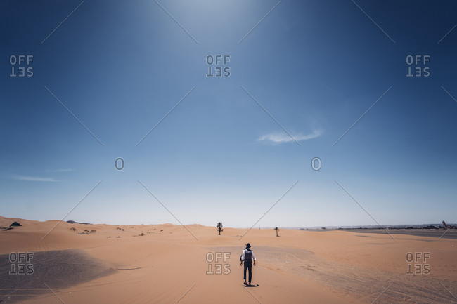 Lonely man with hat walking in the dunes of the desert of Morocco