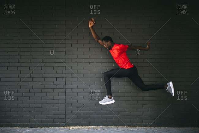 Young sportive man jumping in front of a brick wall