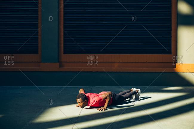 Young sportive man doing pushups outdoors