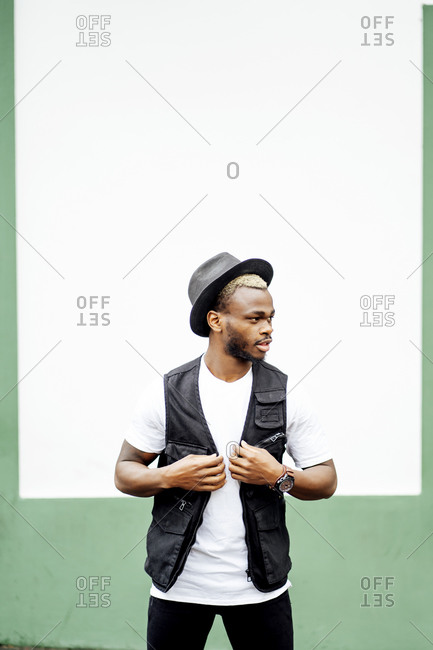 Man wearing hat and looking sideways in front of a green and white wall