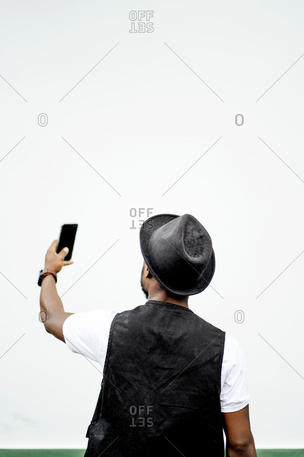 Man using smartphone and taking a selfie in front of a green and white wall