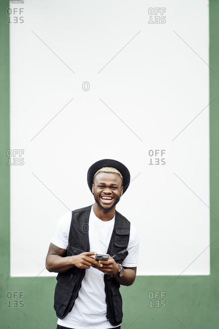 Laughing man using smartphone in front of a green and white wall