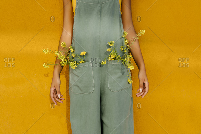 Midsection of woman wearing overalls with yellow flowers in pockets