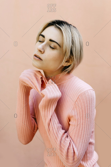 Portrait of young woman with closed eyes wearing pink turtleneck pullover in front of a pink wall