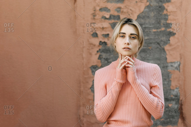 Portrait of blond woman wearing pink turtleneck pullover in front of a pink wall