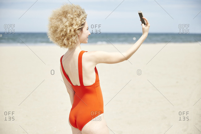 Young woman with curly blond hair taking selfie on the beach