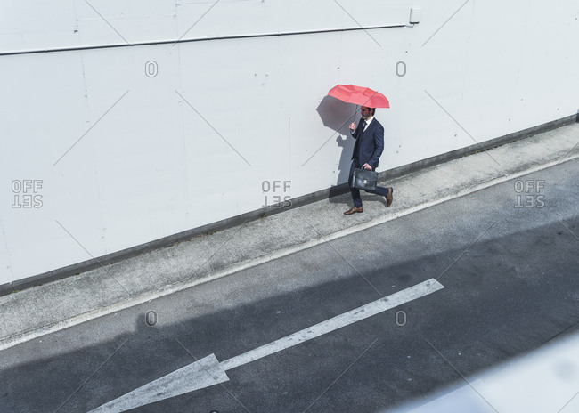 Businessman with umbrella walking at road with arrow sign