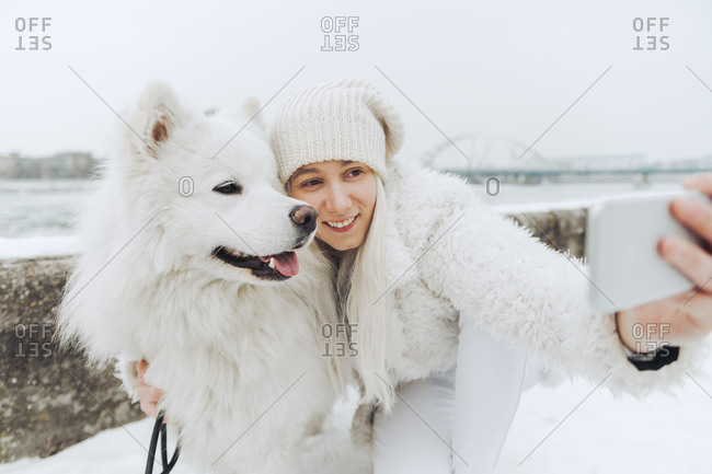 White dressed woman taking selfie with her white dog in winter