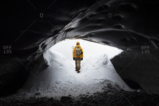 Remote anonymous explorer in warm clothes entering dark snowy cave in cold weather on winter day