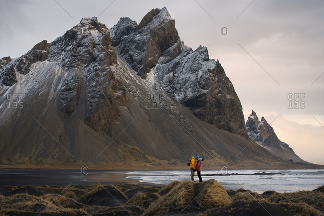 Couple travelers standing on stone on seashore and kissing against rocky mountains in Iceland