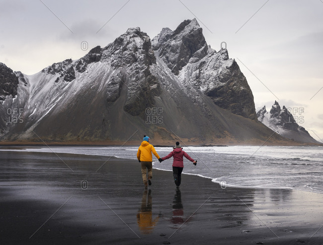Couple travelers walking on seashore holding hands against rocky mountains in Iceland