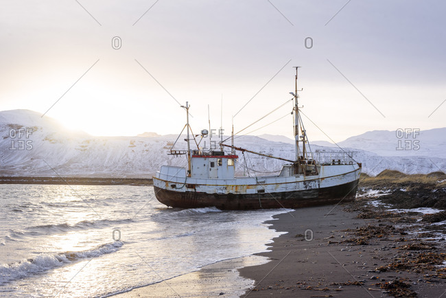 Distant old boat washed by sea surf stranding on shore against backdrop of snowy mountain ranges and beautiful sunset in winter in Iceland