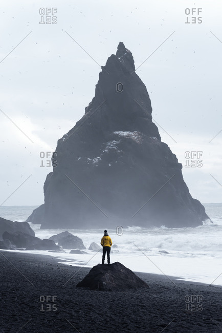 Distant traveler standing on stone on seashore and admiring stormy sea water and huge rough stone rock in middle of sea against cloudy sky in Iceland