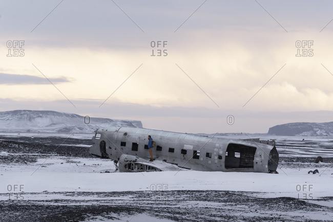 Side view of young man walking on carcass of abandoned aircraft while travelling through Iceland