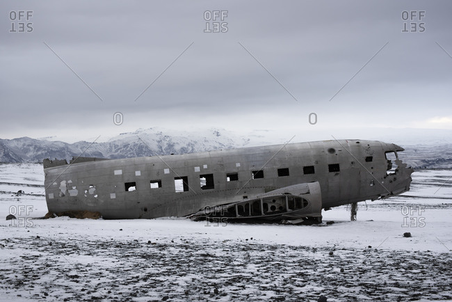Side view of abandoned aircraft lying on snowy landscape of Iceland