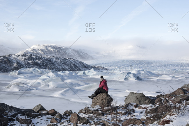 Side view of female traveler in warm clothes sitting on rocky ground near snowy mountain ridge and looking at snowy mountains in winter day