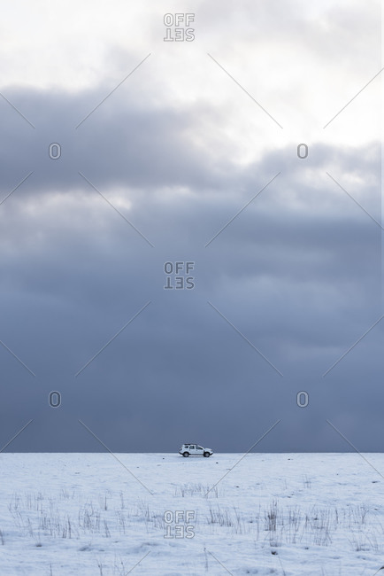 Cold winter landscape with snowy white terrain with white car and remote lonely traveler against backdrop of endless delightful cloudy sky in cold winter