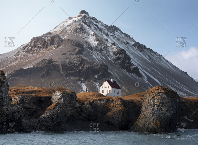 Amazing view of small white secluded house with brown roof and remote traveler locating at foot of snowy mountain on rocky coast against blue sky in winter in Iceland