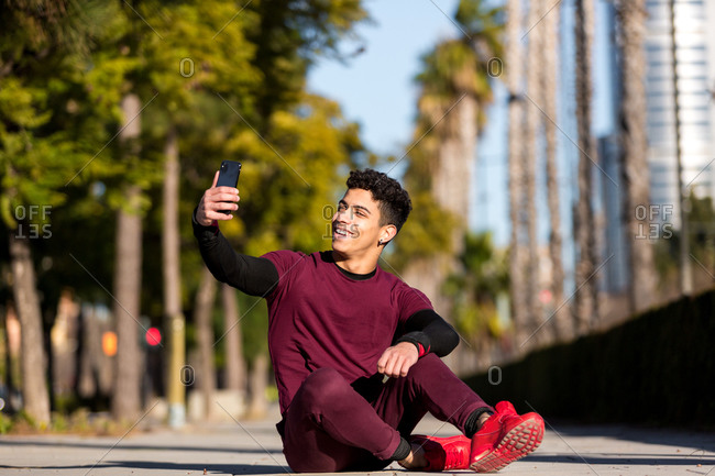 Cheerful young ethnic guy in sportswear smiling and taking selfie while sitting on path during fitness workout on sunny day in city