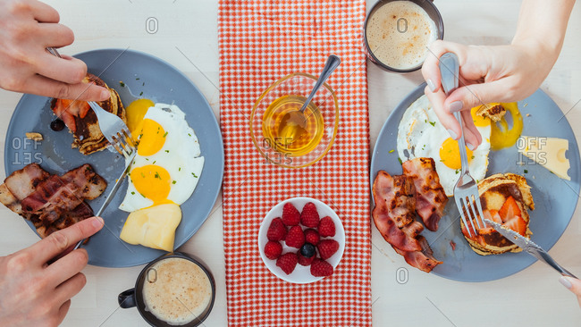 From above view of crop anonymous couple eating tasty fried eggs with cheese and bacon and pancakes with berries for breakfast at home