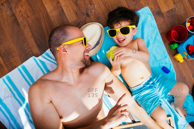 From above view of cheerful boy in yellow sunglasses and blue swimwear smiling while feeding father apple lying on towels together having beach at home