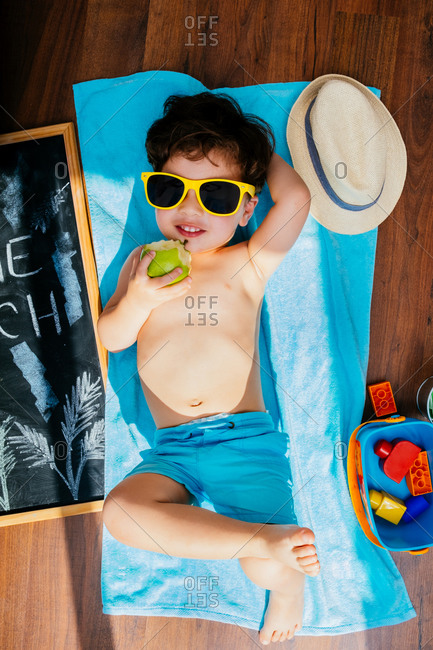 From above view of cheerful little boy in yellow sunglasses and blue swimwear eating apple while lying on towel on floor having home beach on quarantine