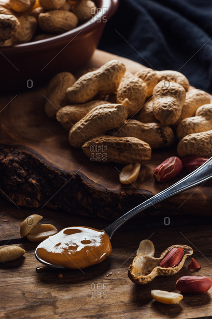 Group of peanuts on wooden boards and spoon with peanut butter