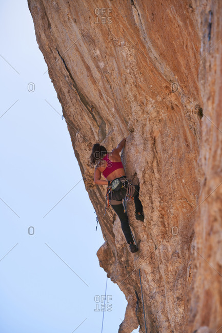 From bellow active female alpinist in sportswear with rope and safety equipment ascending rocky slope of high mountain on sunny day