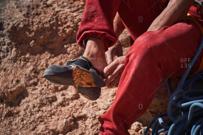 Unrecognizable male alpinist in red sportswear sitting on rocky ground near blue rope and wearing climbing shoes before climbing