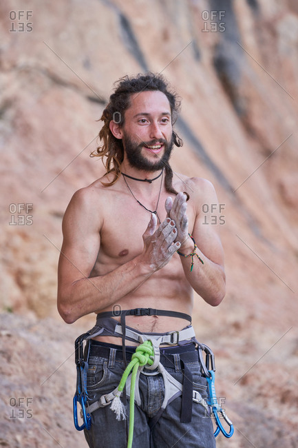 Positive muscular shirtless bearded alpinist in safety gear standing with hands together and resting after practicing climbing on rocky slope