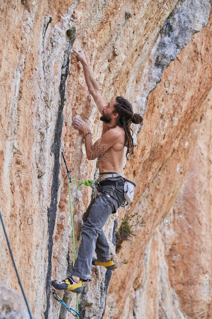 From below side view of shirtless bearded alpinist in safety equipment climbing up on rocky slope of mountain and looking up