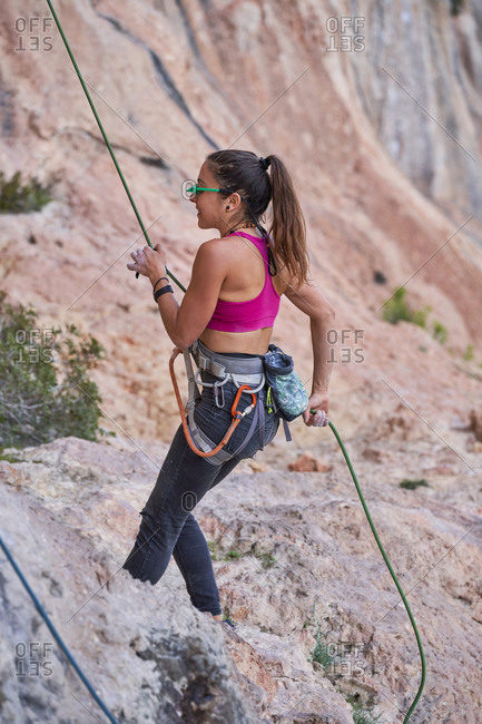 Side view of active young woman in safety gear and belay glasses standing with rope in hands and preparing for climbing rock