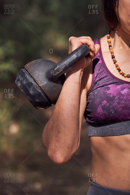 Crop young female athlete wearing sportive top and pushing up medium weight to chest while doing workout at sunny park
